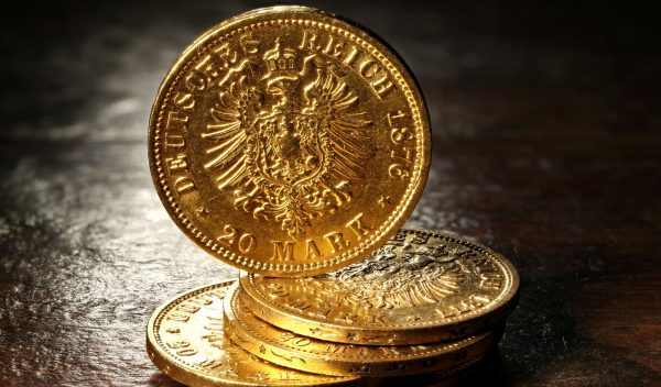 Hamburg gold coins (German Empire Goldmark) on rustic wooden bac